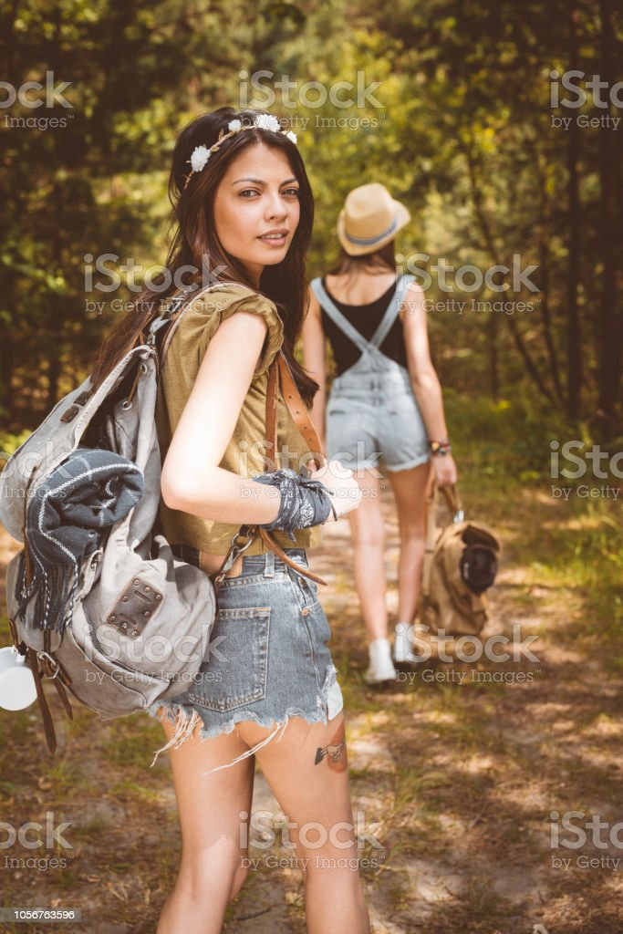 Young woman walking in the forest Outdoor shot of two young women walking in the forest, holding backpacks. Beautiful brunette smiling at the camera. 20-24 Years Stock Photo