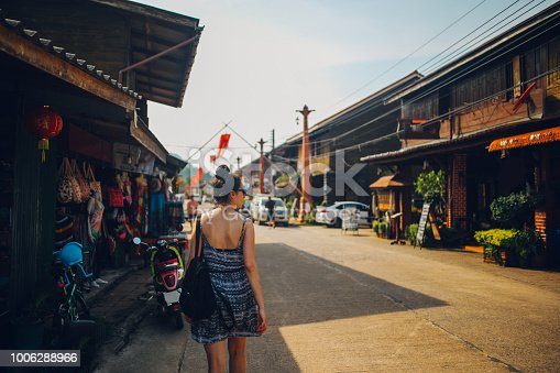 Vintage toned image of a young tourist woman, traveling solo, walking on the streets of the Koh Lanta Old Town, in Thailand.