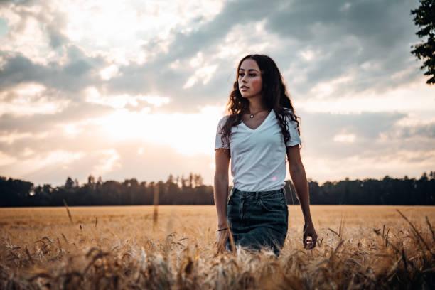 Young woman walking inside in summer corn field stock photo
