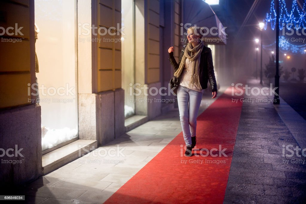 Young Woman Walking next to a Glowing Store Display stock photo