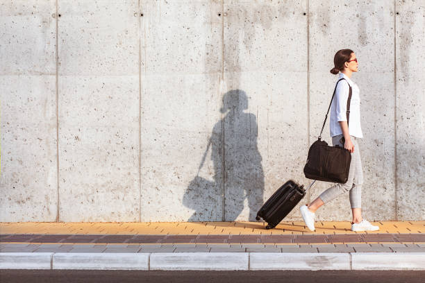 Young woman walking on a sidewalk beside the concrete wall and pulling a small wheeled luggage stock photo