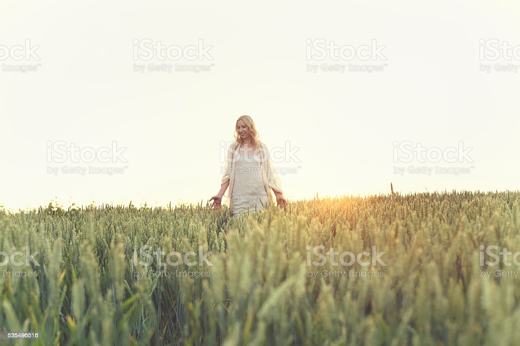 young woman walking on a wheat field on sunset stock photo
