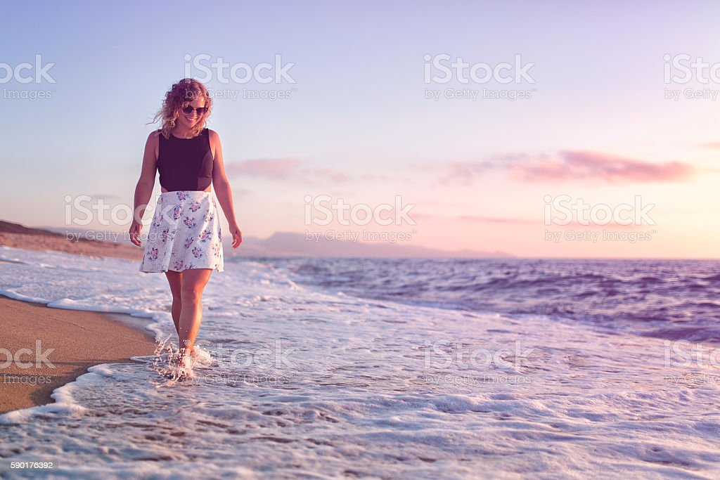 Young woman walking on beach at sunset – Foto