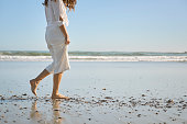 Young woman dressed in white walking barefoot in the water seaside path
