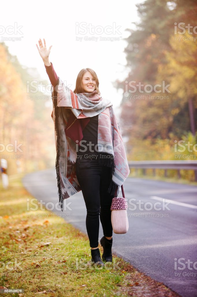 young woman walking on street in autumn and waving stock photo