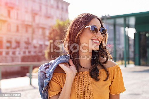 istock Young woman walking on street 1134003334