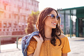 Happy latin woman holding denim jacket and walking on the street on a bright sunny day. Cheerful stylish girl with sunglasses enjoying the spring. Young woman wearing shades while looking away in the afternoon.