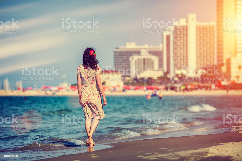 Young woman walking on the beach in Tel Aviv, Israel stock photo