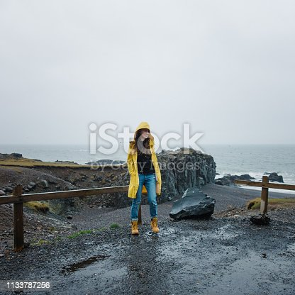 Young woman walking on the beach on a rainy day in Iceland