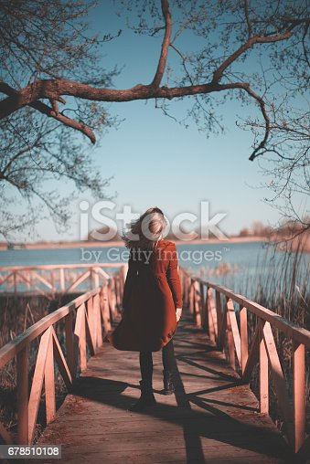 Woman in red dress walking on the wooden bridge. Clear sky and a lake on the background.