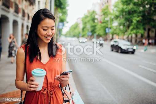 Happy young woman walking on the city street after shopping and using her smartphone