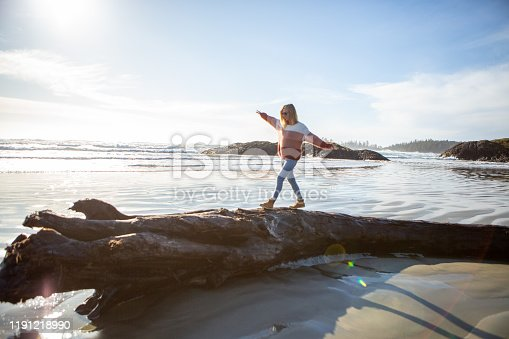 Young woman walking on tree trunk on beach balancing body weight