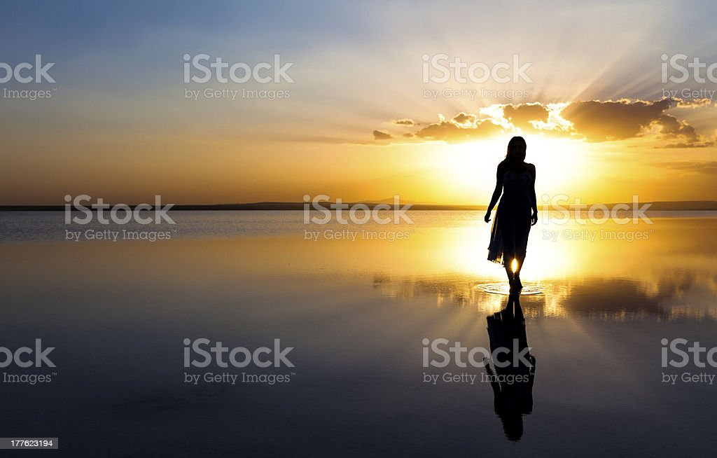 Young woman walking on water at sunset stock photo