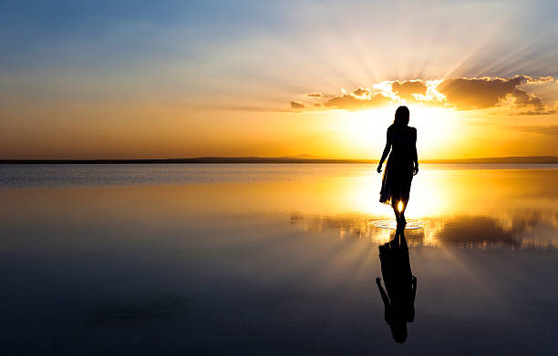 Young woman walking on water at sunset Beautiful woman walking on a gorgeous lake eternity stock pictures, royalty-free photos & images