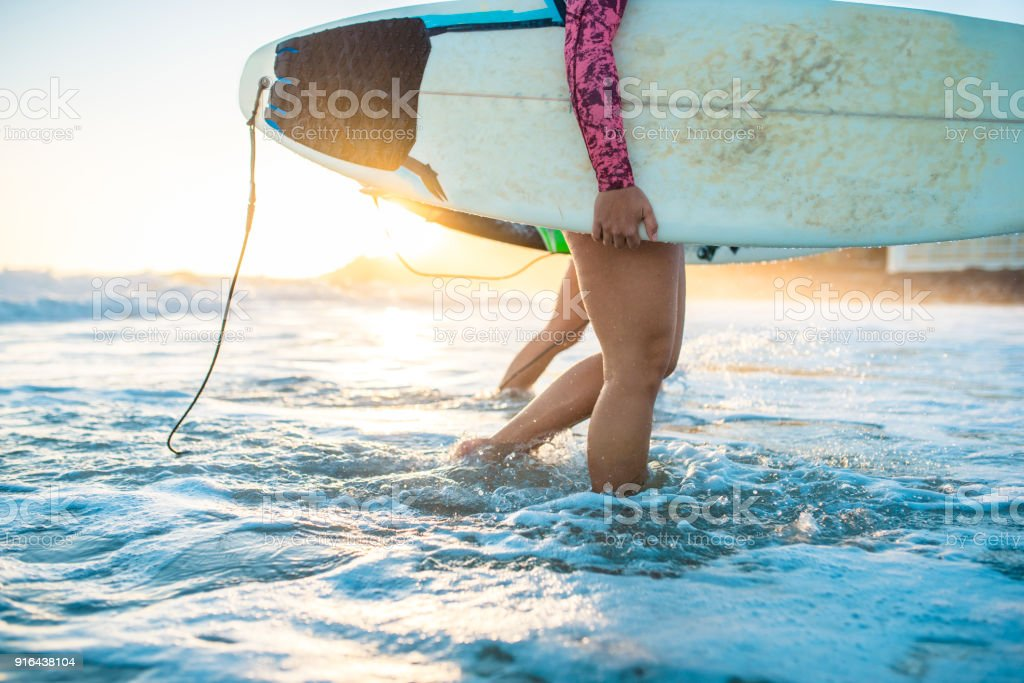 Young woman walking out of the ocean with her surfboard stock photo