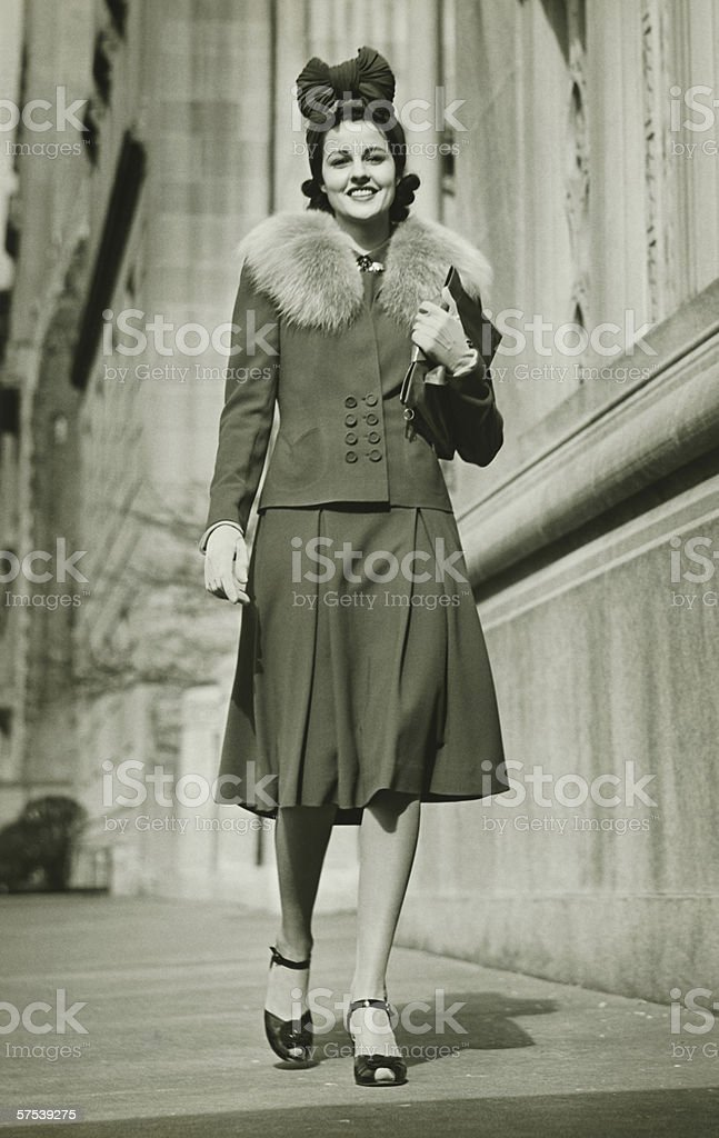 Young woman walking outdoors, (B&W) stock photo