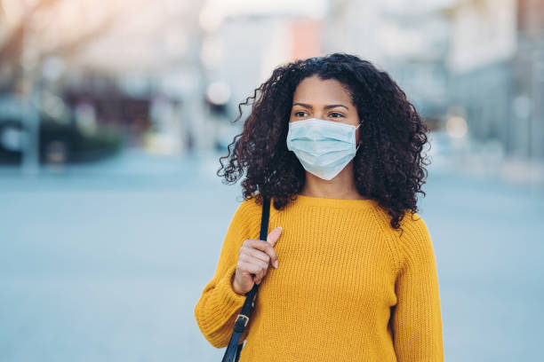 Young woman walking outdoors with a face mask stock photo