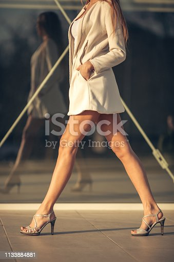 Beautiful elegance young woman walking over sidewalk in front of store windows.