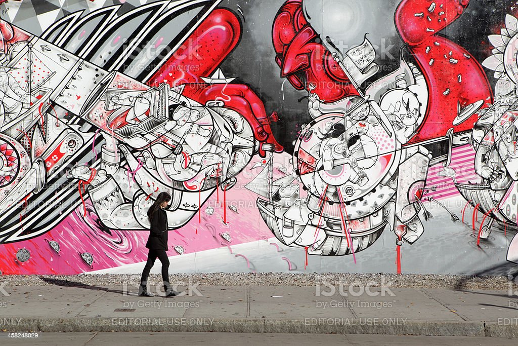 NYC young woman walking past How Nosm street art mural stock photo