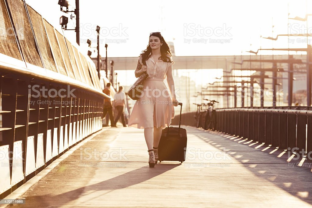 Young woman walking sidewalk and carrying suitcase Young woman wearing blouse and skirt walking down the sidewalk in the city at sunset, carrying suitcase. Monochrome picture. 2015 Stock Photo
