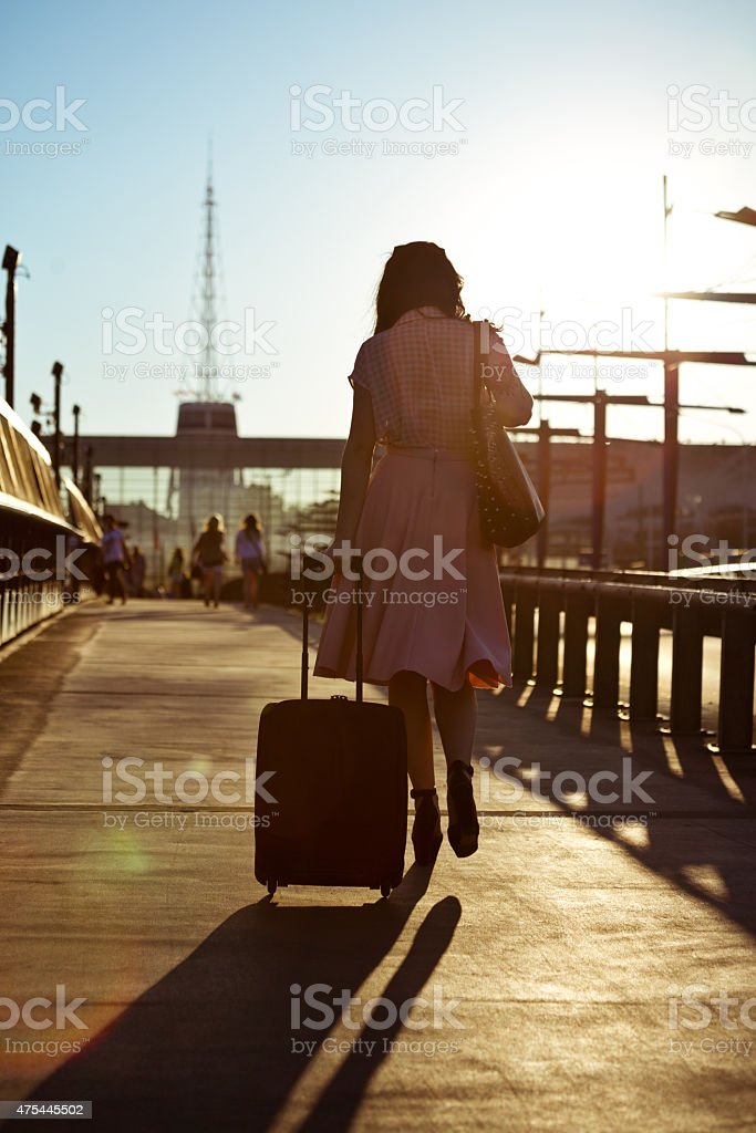 Young woman walking sidewalk and carrying suitcase Back view of young woman wearing blouse and skirt walking down the sidewalk in the city at sunset, carrying suitcase.  2015 Stock Photo