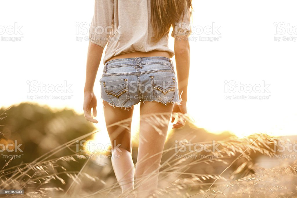 Young woman walking through a field of tall grass stock photo