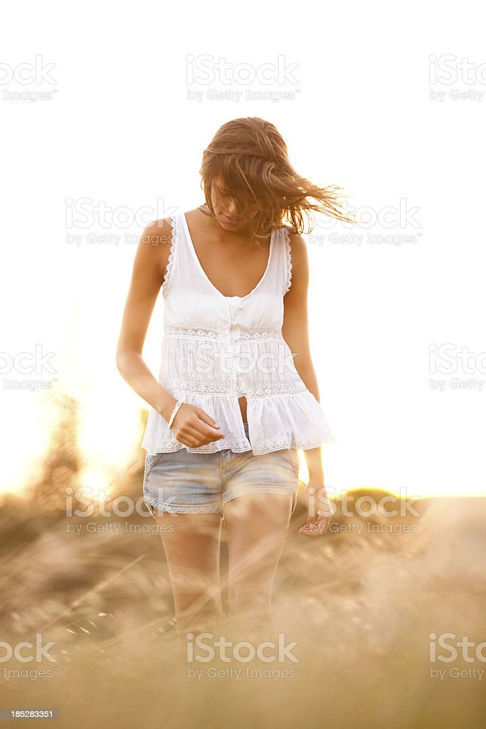Young woman walking through a field searching for something royalty-free stock photo
