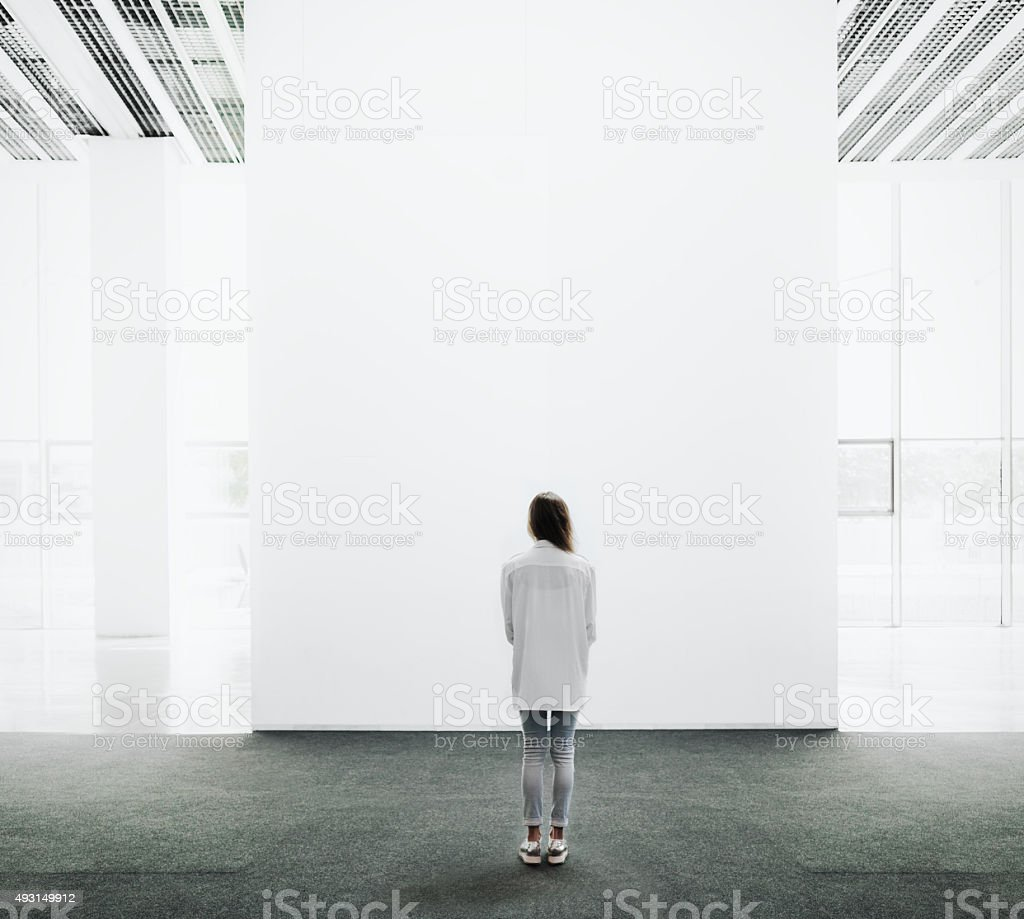 Young woman walking through a gallery and looking at the stock photo