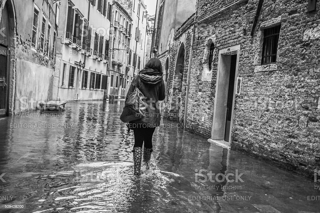 Young woman walking through the flooded streets of Venice stock photo