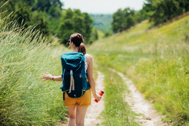 Young woman walking through the mountain paths and enjoying stock photo
