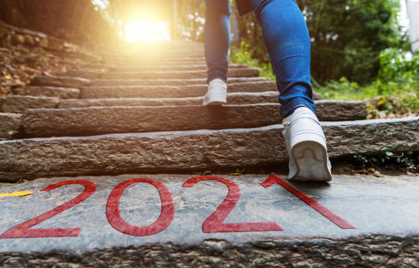Young woman walking up stone stairs with number 2021 stock photo