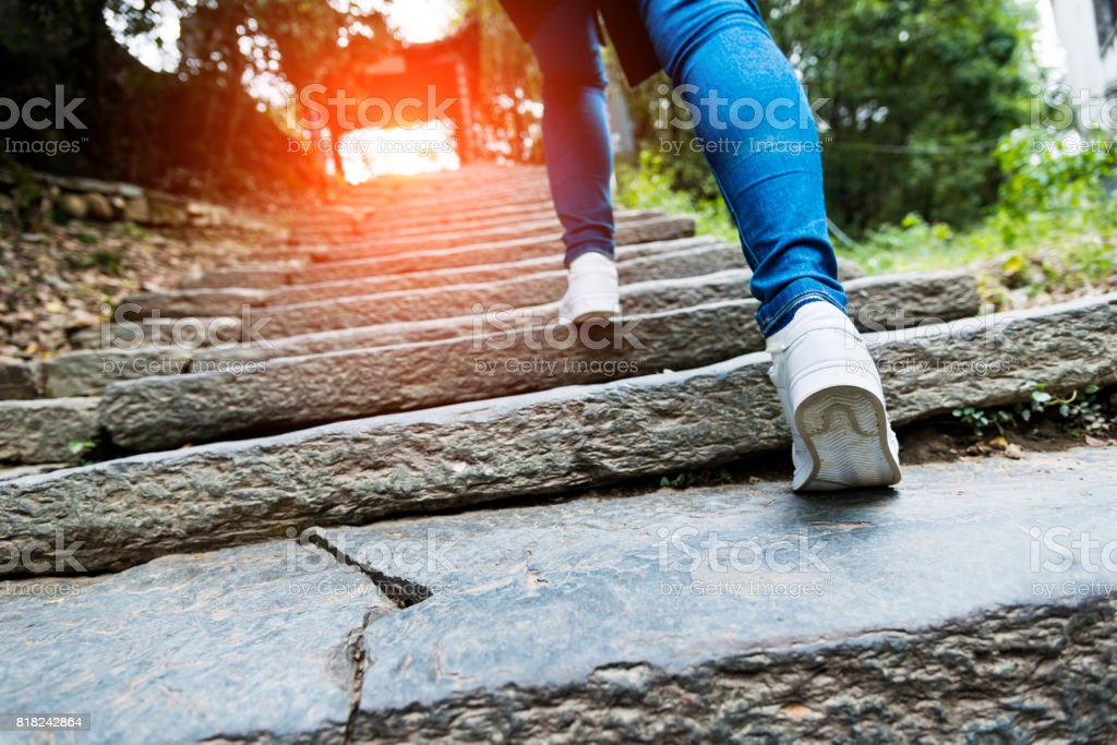 Young woman walking up the stone stairs stock photo