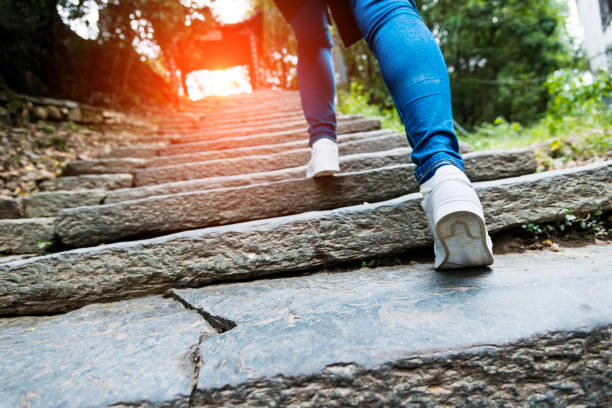 young woman walking up the stone stairs - staircase stock photos and pictures