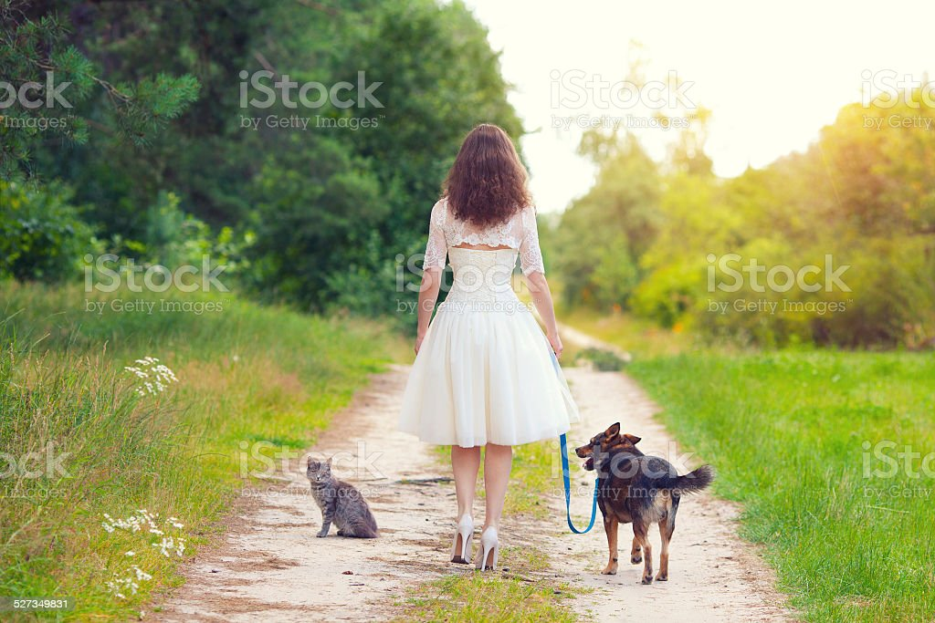 Young woman walking with dog and cat stock photo