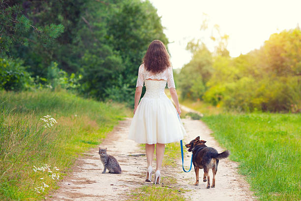 Young woman walking with dog and cat Young woman walking with dog and cat on the rural road sun shining through dresses stock pictures, royalty-free photos & images