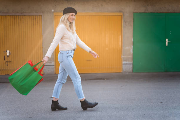 Junge Frau zu Fuß mit grünen und roten Einkaufstaschen im Freien von Garagen Stock Foto – Foto