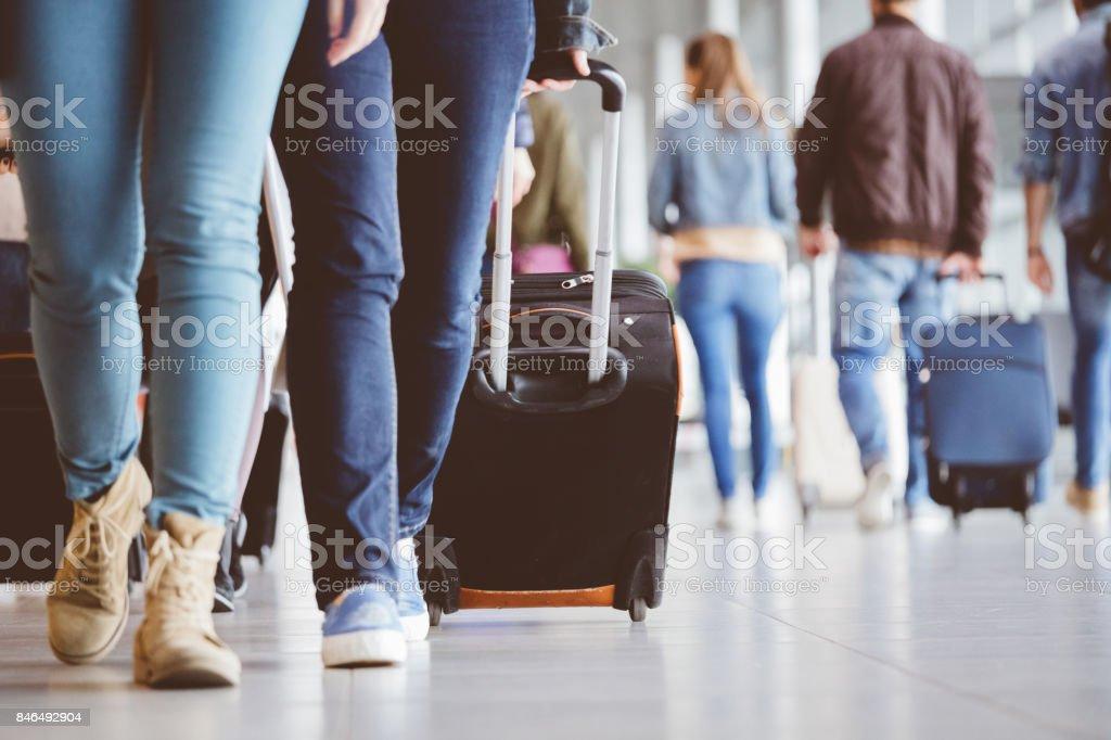 Junge Frau zu Fuß mit Gepäck am Flughafen – Foto