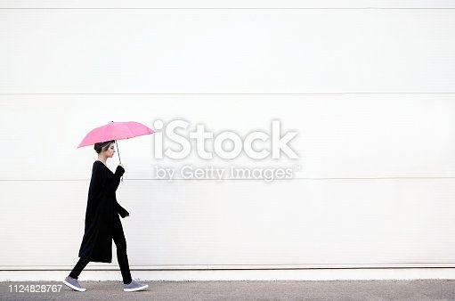 Young woman in black clothes walking with pink umbrella