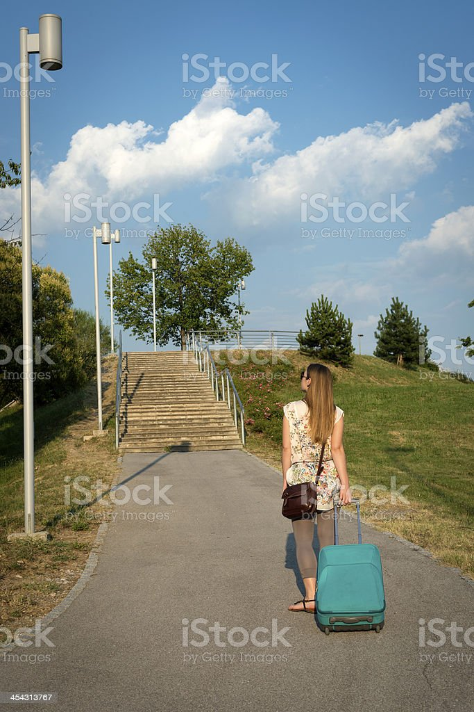 Young Woman Walking with Rolling Sitcase royalty-free stock photo