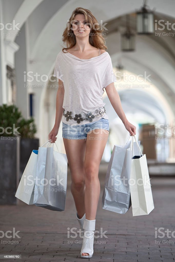 Young woman walking with shopping bags in city stock photo