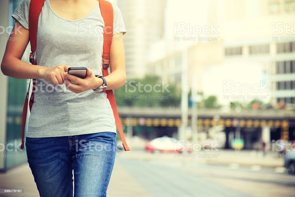 young woman walking with smart phone in modern city - foto de acervo