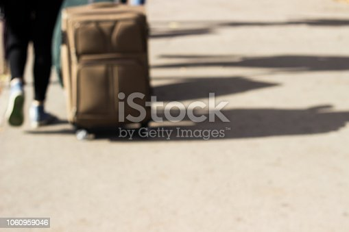 1060957508 istock photo Young woman walking with suitcase 1060959046