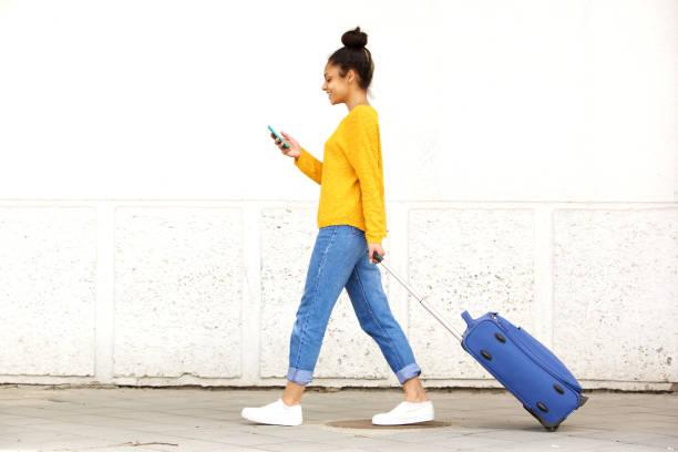 junge frau zu fuß mit reisetasche und handy - handytasche stock-fotos und bilder