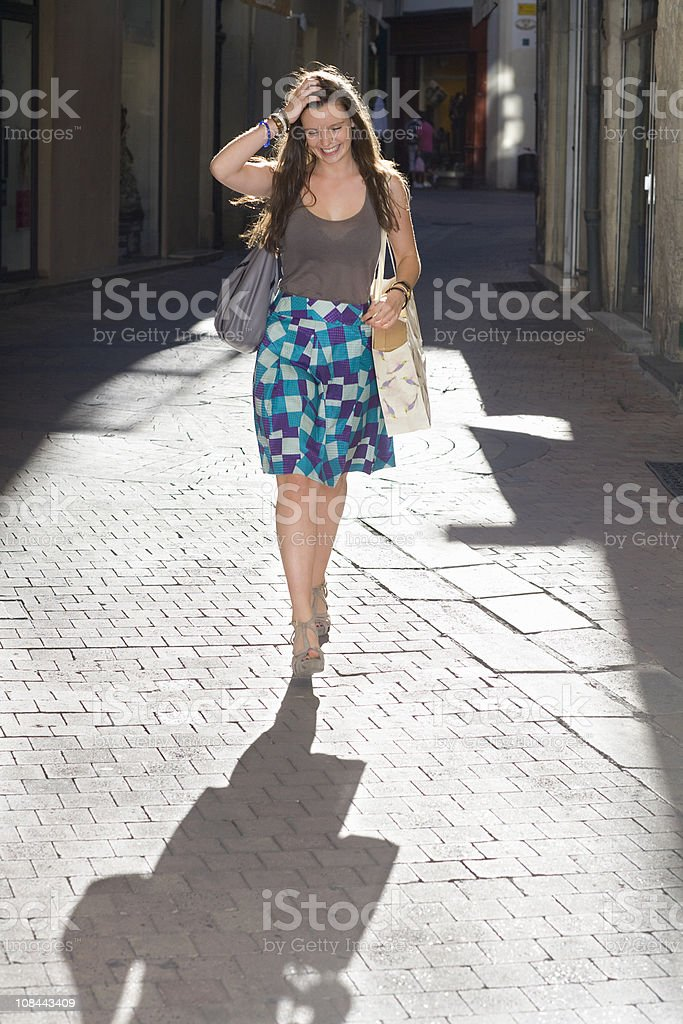Young woman walks in street with bags stock photo