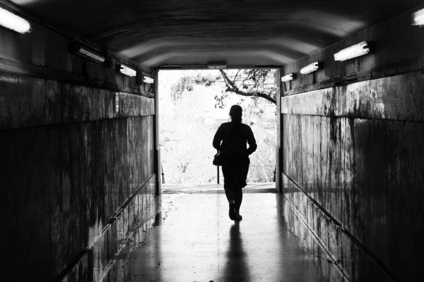 young woman walks out of a dimly lit tunnel into a bright sunny town - port bou 25/03/2017 - dimly stock pictures, royalty-free photos & images
