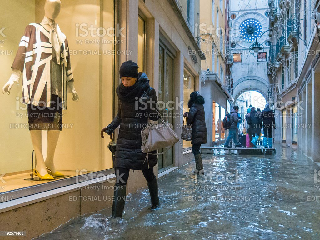 Young woman walks through the acqua alta waters of Venice stock photo