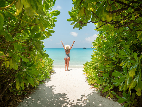 Rear view of woman walking on white sand beach relaxing and sunbathing by the sea lagoon in the Maldives