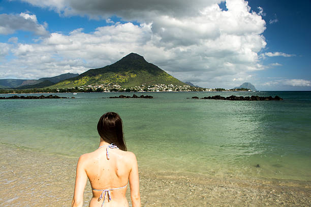 Young woman walks towards the ocean in bikini stock photo