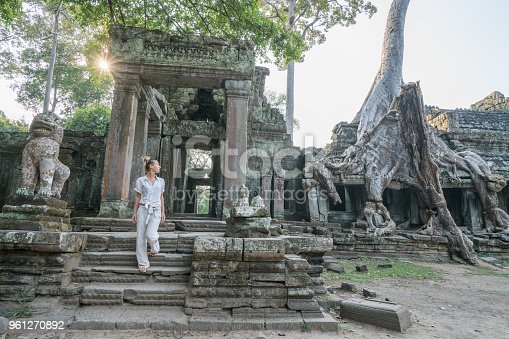 Young woman traveling in Cambodia visiting the temples of Angkor wat complex. People travel discovery Asia concept. Shot at sunset, one woman only, adventure and exploration in Siem Reap, Southeast Asia.