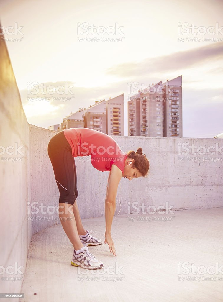 Young woman warming up for run at urban place royalty-free stock photo